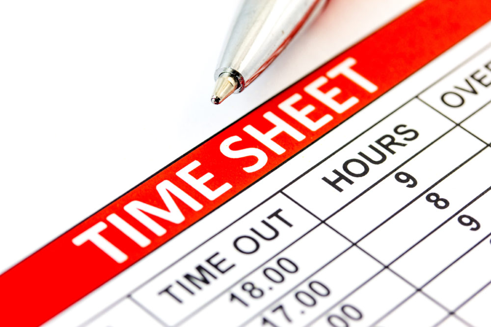 Compiled Time and Attendance sheet with a pen - business concept